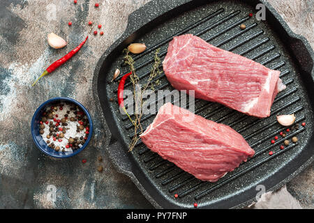 Fresh raw beef meat in a grill pan. Two pieces of beef with spices for cooking. View from above. - Stock Photo