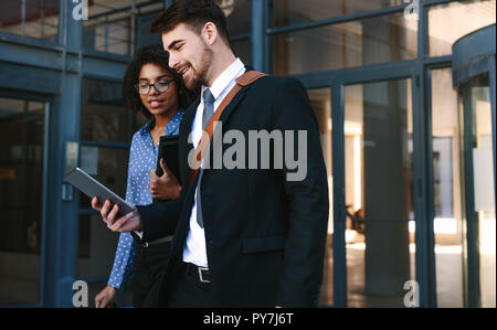 Business professionals walking out of corporate building with a digital tablet. Businessman and woman with digital tablet walking out of office. - Stock Photo