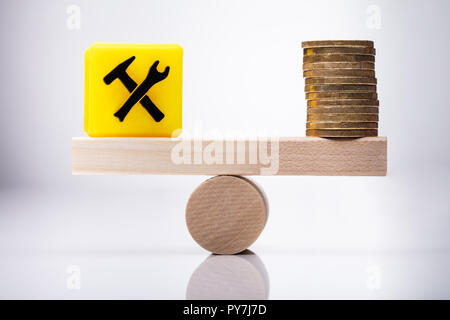 Yellow Under Construction Icon Cubic Block And Stacked Coins Balancing On Wooden Seesaw - Stock Photo