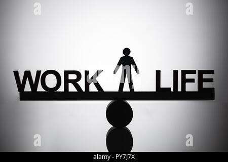 Silhouette Of A Human Figure Standing Between Work And Life Balance On Seesaw - Stock Photo