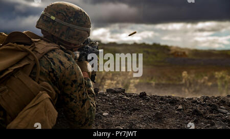 A U.S. Marine with Lima Company, 3rd Battalion, 3rd Marine Regiment engages his targets during Exercise Bougainville II at the Pohakuloa Training Area, Island of Hawaii, Oct. 20, 2018. Exercise Bougainville II is the 2nd part of the pre-deployment workup focusing on platoon and company level exercises. (U.S. Marine Corps photo by Sgt. Ricky Gomez) - Stock Photo