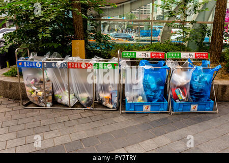 Seoul, South Korea - June 20, 2017: Waste sorting containers with colored inscriptions for plastic, glass bottles and paper in the downtown in Seoul. - Stock Photo
