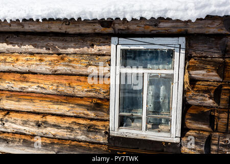 Old- fashioned wooden window in winter, roof of the house covered with snow - Stock Photo