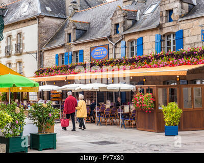 Brittany French Rustic alfresco restaurant 'La Port Au Vin' with mature vacation couple strolling Ville Close de Concarneau Bretagne Finistere France - Stock Photo