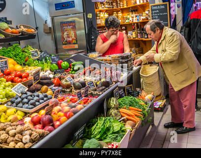 CONCARNEAU fruit & vegetable market stall with mature shopper counting & paying for produce in euros coins, Halles Market Concarneau Brittany France - Stock Photo