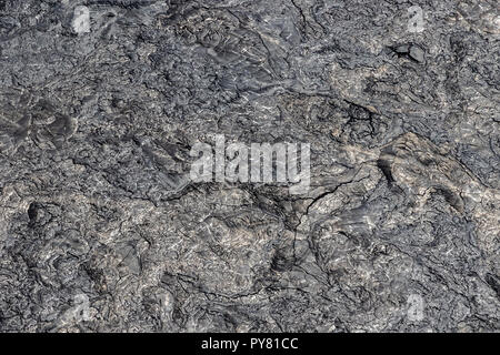 Aerial view of Puu Ooo Volcanic pahoehoe lava field from recent eruption. The surface is swirled and wrinkled, cracks from cooling. - Stock Photo