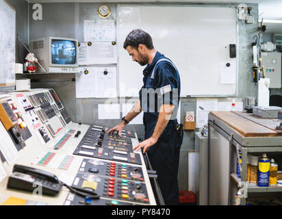 Marine engineer officer working in engine room - Stock Photo
