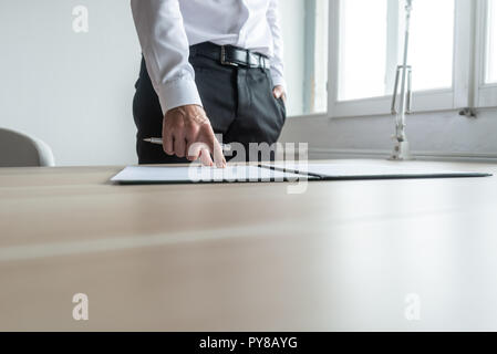Businessman standing at his desk pointing to a document in folder where to sign. - Stock Photo