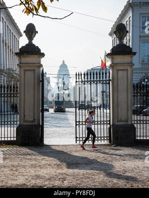 Brussels, woman runninfg in the Bruxelles park, behind Statue of King Albert and Law Courts of Brussels - Stock Photo