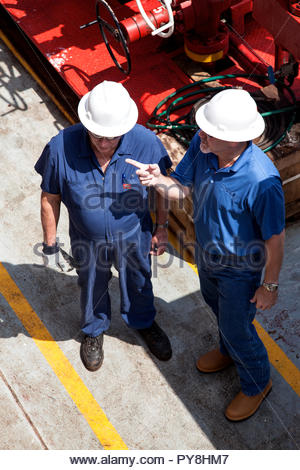 High angle view of workers pointing on offshore oil platform - Stock Photo
