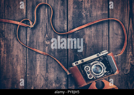 Old retro vintage camera on grunge wooden background - Stock Photo