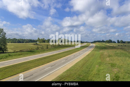 Sunlit four lane road in rural setting with clouds - Stock Photo