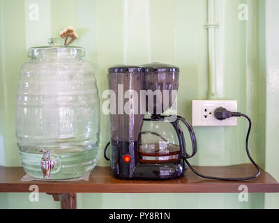 Cooler bottle and electric kettle with plug on wooden shelf on light green container wall background in cafe. - Stock Photo