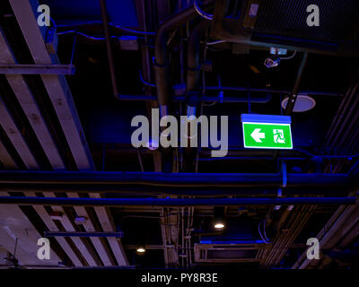 Illuminated green fire exit LED light sign on the ceiling in the dark with pipe line system inside the building. - Stock Photo