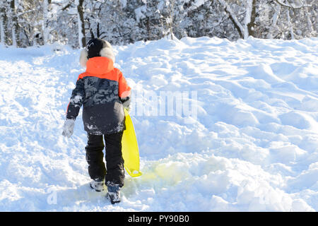 Boy pulling a sled up the hill, winter fun - Stock Photo