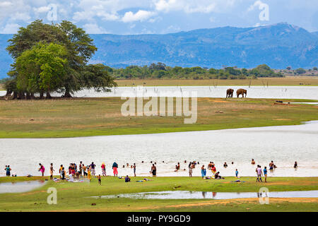 People washing in the lake and elephants in the background, in Uda Walawe, Sri Lanka. - Stock Photo