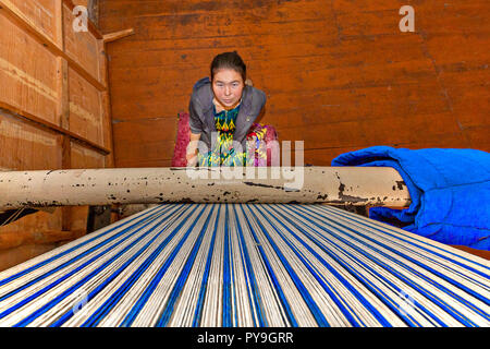 Local girl weaving rug and looks up the weaving loom, in Nukus, Uzbekistan - Stock Photo