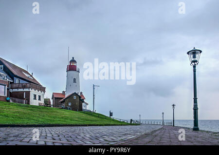 Urk, The Netherlands, October 24, 2018: Sea promenade with lighthouse and lanterns on the shore of the former sea, now lake IJsselmeer, on a rainy aft - Stock Photo