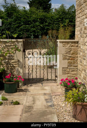 metal gateway with stone wall and pathway leading into English Garden,England,Europe - Stock Photo