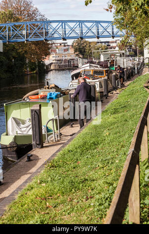 Men working on tethering their boats at Teddington,London,England,UK - Stock Photo