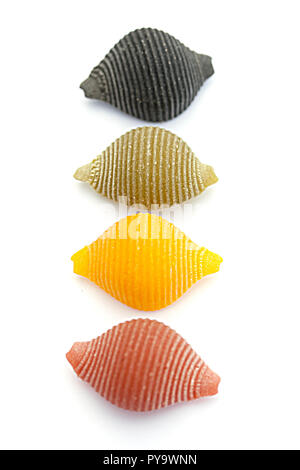 Four pasta shells: red, black, green and yellow - Stock Photo