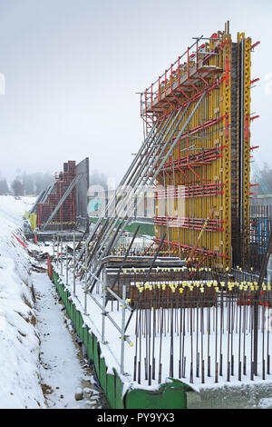 A large construction site in Scotland with work halted by heavy snowfall. Shows large formwork panels for the building of tall concrete walls. - Stock Photo