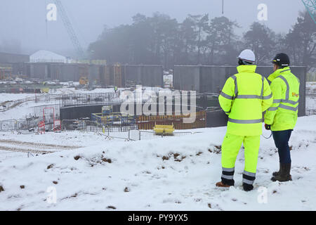 Two construction workers view a large building site in Scotland with work halted by heavy snowfall - Stock Photo