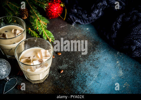 Irish cream cocktail or liqueur, traditional winter christmas drink, dark rusty background with fir tree branches, coffee beans and christmas decorati - Stock Photo