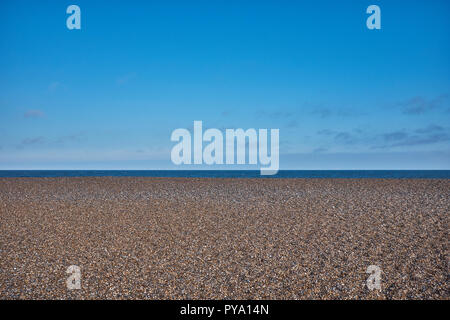 Pebble beach with no people at Clay On Sea with large amount of blue sky and small amount of sea - Stock Photo