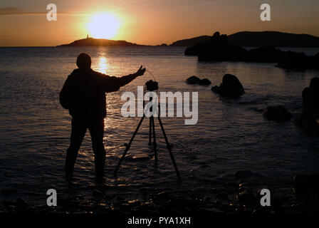 Self portrait of the photographer taking a picture of Little Ross Island from Torrs Point across Kirkcudbright Bay, Dumfries and Galloway, SW Scotland. his DSLR is on a tripod and he uses a cable release. He points the camera into the setting sun behind the island - Stock Photo