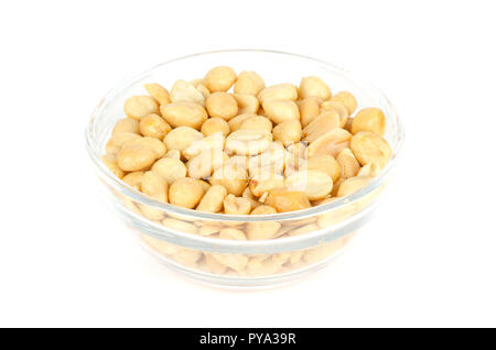 Roasted and salted peanuts in glass bowl. Shelled Arachis hypogaea, also called groundnut or goober, used as a snack. Isolated macro food photo. - Stock Photo