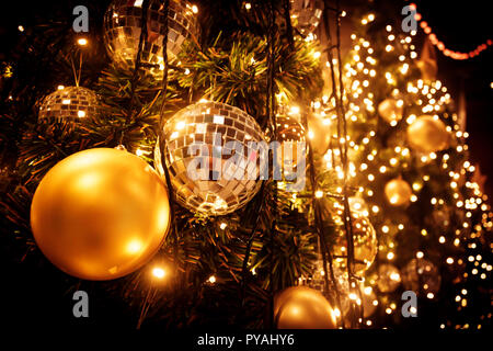 Christmas tree with gold ball and bokeh lights background. Xmas abstract close up with glowing decorations outdoors. - Stock Photo