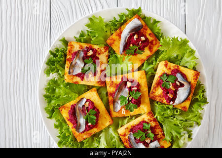 overhead view of Fried Polenta Squares with Creamy beetroot puree, topped with anchovies and garnished with fresh parsley on a white plate on a wooden - Stock Photo
