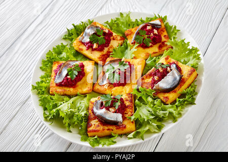 tasty Fried Polenta Squares with Creamy beetroot puree, topped with anchovies and garnished with fresh parsley on a white plate on a wooden table, hor - Stock Photo