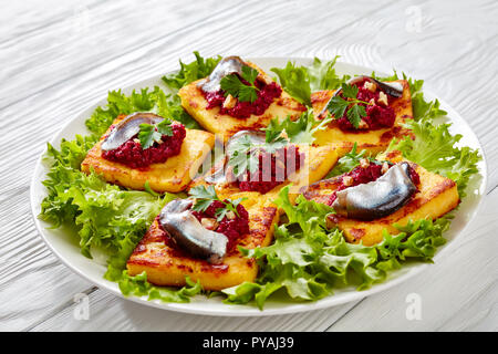 crispy Fried Polenta Squares with Creamy beetroot puree, topped with anchovies and garnished with fresh parsley on a white plate on a wooden table, ho - Stock Photo