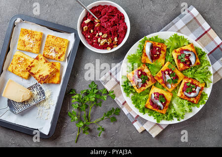 Polenta Squares with Creamy beetroot puree, topped with anchovies and parsley on a white plate. freshly baked polenta bars and parmesan on a baking tr - Stock Photo
