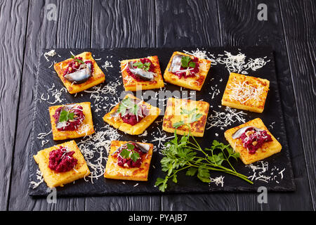 close-up of Polenta Squares open sandwiches with Creamy beetroot pate, topped with anchovies and parsley served on a black stone tray on a wooden tabl - Stock Photo