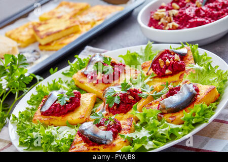 close-up of Polenta Squares with Creamy beetroot puree, topped with anchovies and parsley on a white plate. freshly baked polenta bars and parmesan on - Stock Photo