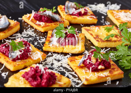 close-up of portions of Polenta Squares with Creamy beetroot pate, topped with anchovies and parsley served on a black stone tray on a wooden table, v - Stock Photo