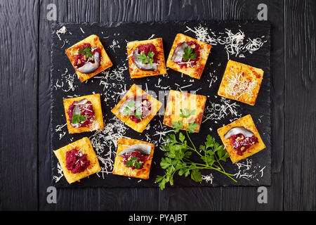 overhead view of portions of Polenta Squares with Creamy beetroot pate, topped with anchovies and parsley served on a black stone tray on a wooden tab - Stock Photo