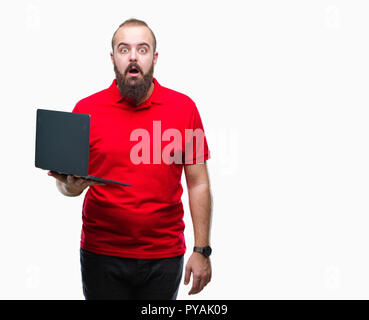 Young caucasian man using computer laptop over isolated background scared in shock with a surprise face, afraid and excited with fear expression - Stock Photo