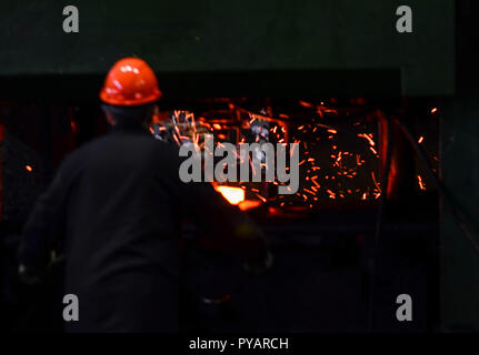 Hot iron in smeltery held by a worker. Heavy industry metallurgical plant sparks stove metall. Forge, blacksmith on the background of flying sparks. R - Stock Photo