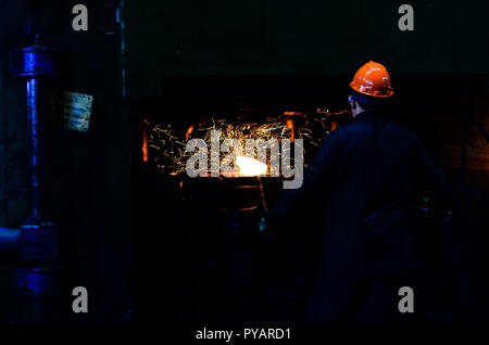 Industrial Worker at the factory welding closeup. Hot iron in smeltery held by a worker. Iron melting recycling work. Roll of hot metal. Heavy forging - Stock Photo