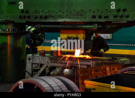 Detail - form part of a cast machine. Hot iron in smeltery held by a worker. Heavy forgings Plant. Metal work - Stock Photo