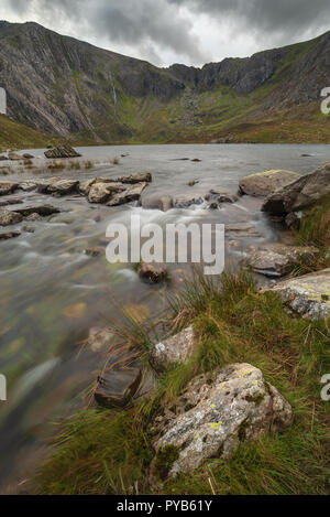 Landscape image of river flowing down mountain range near Llyn Ogwen and Llyn Idwal in Snowdonia in Autumn - Stock Photo