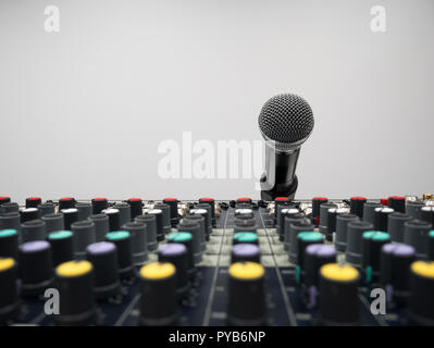Audio mixer console in studio with microphone at background - Stock Photo