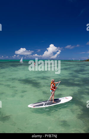 Tourist stand up paddle boarding on the north coast of Mauritius. - Stock Photo