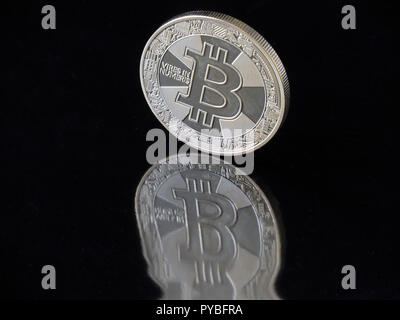 Berlin, Germany. 30th Aug, 2018. 30 August 2018, Germany, Berlin: A Bitcoin coin with the imprint 'Vires in Numeris' (strength in numbers) reflects distorted in a black area. The digital currency has been around for ten years now and is based on blockchains (chains of data blocks) in which Bitcoin units are generated in mathematical operations on the computer. Credit: Soeren Stache/dpa-Zentralbild/ZB/dpa/Alamy Live News - Stock Photo