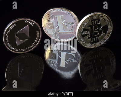 30 August 2018, Berlin: 30 August 2018, Germany, Berlin: A (L-R) Etherum Classic coin with the imprint 'ETH', a Lite coin and a Bitcoin coin with the imprint 'Vires in Numeris' (strength in numbers) are reflected distorted in a black surface. The digital currency Bitcoin has been around for ten years now and is based on blockchains (chains of data blocks), in which Bitcoin units are generated in mathematical operations on the computer. After Bitcoin, the Internet currency Etherum is the world's second largest virtual payment method. Photo: Soeren Stache/dpa-Zentralbild/ZB - Stock Photo
