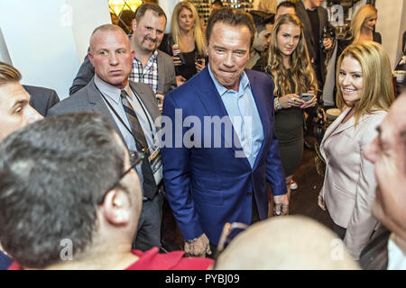 Columbus, Ohio, USA. 3rd Mar, 2017. ARNOLD SCHWARZENEGGER and his girlfriend HEATHER MILLIGAN (in pink right) mingle with the crowd at the Arnold Experience Friday, March 3, 2017 at the Wolfe Circus House in Columbus, Ohio. The event is held each year to raise money for the After-School All-Stars Ohio which provides quality after-school programs for children in need and features celebrities and VIPs from the Arnold Classic body building event. Credit: James D. DeCamp/ZUMA Wire/Alamy Live News - Stock Photo